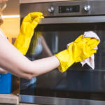 young smiling woman in protective glove with rag cleaning oven.